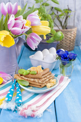 Homemade traditional pancakes with parmesan and basil for spring carnival. Italian breakfast. Bright flowers of tulips. Blue background. A free place for text or a postcard.