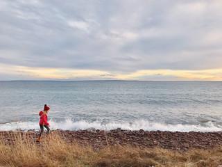 Girl walking along the beach, Tonsberg, Vestfold, Norway