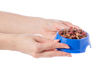 Food for dogs and cats in a blue bowl in hand