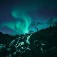Northern lights over waterfall, Lofoten, Norway