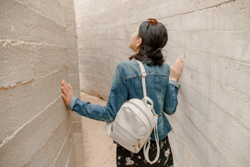 Attractive young woman standing between concrete walls. Caucasian girl in casual jeans looks up.