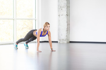 Fitness, sport concept. Woman in loft interior doing push up