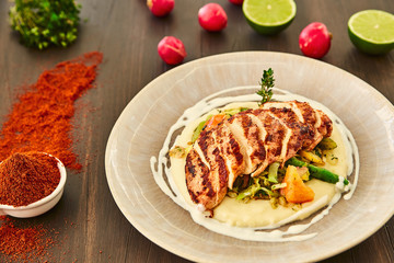 Grilled chicken fillet is cut into slices on a cushion of mashed potatoes with vegetables - onion, garlic, pepper, cabbage, radish, greens in a large beige dish on a dark wooden table.