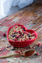 Red heart bowl filled with granola with dried red and blue berries on red rustic table