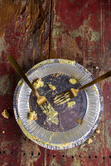 Empty pie tin with two forks on rustic wood table top view