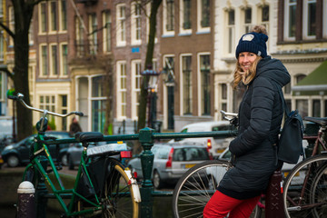 Tourist in Amsterdam - woman in her 30s waiting beside bicycles on a bridge in Amsterdam