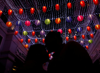 A couple kiss below Chinese lanterns during a countdown welcoming the Chinese Lunar new year in Binondo district, metro Manila