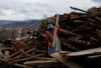 A woman handles a piece of wood in Killiri, La Paz