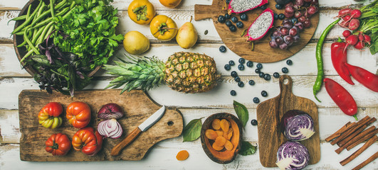 Helathy vegan food cooking background. Flat-lay of Fresh fruit, vegetables, greens and superfoods on boards over white wooden table, top view, wide composition. Clean eating, alkaline diet concept