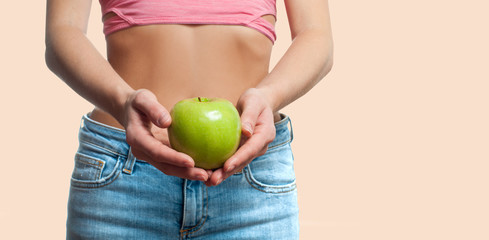 Diet concept. Beautiful woman with slim waist is holding apple on pastel background