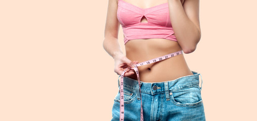 Woman is measuring waist after weight loss on faded pastel background