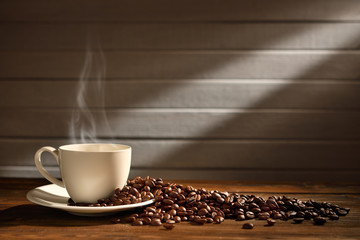 Cup of coffee with smoke and coffee beans on wooden background, This image with no smoke is available