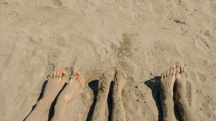 Bare feet of a family on the shore. Legs in the sand. The feet are sprinkled with sand.