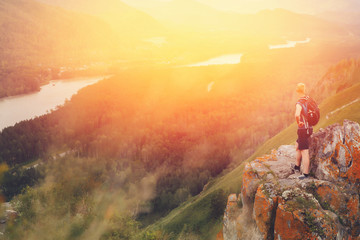 Tourist plaid shirt and with backpack standing on top of mountain and having fun against backdrop of mountains, rivers. setting sun