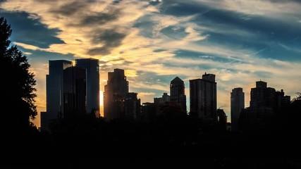 Fotobehang - Sun setting behind buildings silhouettes New York City skiline sunset timelapse.