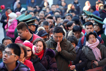 People wait to enter a hall to pray for good fortune at Lama Temple on the first day of the Year of the Dog in Beijing