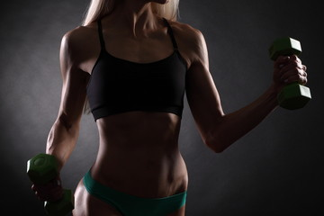 slim muscular girl with dumbbells
