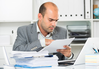 Businessman in shirt viewing documents at the table