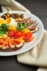 Bruschetta, assorted, different fillings, on plates with a soft-boiled egg in the middle