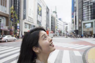 都会の交差点で空を見上げる女性。