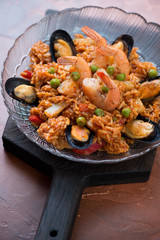 Portion of spanish seafood paella with mussels, tiger shrimps, calamari, green peas and red bell pepper, selective focus