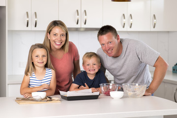 young happy couple baking together with little son and young beautiful daughter at home kitchen having fun playing with cream