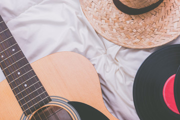 acoustic guitar, record & hat on white bed. relaxation and travelling concept