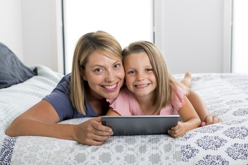 blond Caucasian mother lying on bed with her young sweet 7 years old daughter using internet on digital internet tablet pad together at home