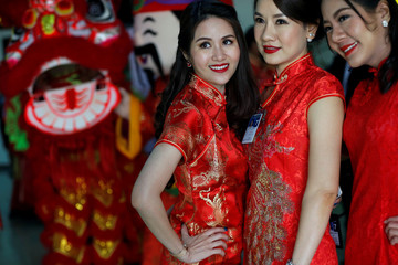 Thai women pose for photo as they attend a Warm Welcome ceremony to Chinese tourists in Bangkok