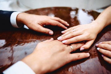 Bride's hands on the table with drops of water during rain with reflection
