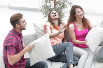 cheerful friends playing with the pillows sitting on the couch