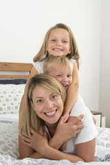 young blond Caucasian woman lying on bed together with her little sweet 3 and 7 years old son and daughter laughing playing happy at home