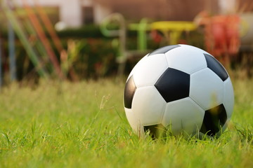 Football or soccer ball on green grass playground background,outdoor activities.
