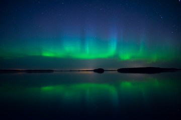 Wall Mural - Northern lights dancing over calm lake. Farnebofjarden national park in Sweden