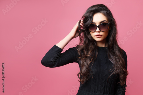 6d7f0cb0f Beautiful High fashion woman posing in studio. Gorgeous brunette model girl  with beautiful hairstyle wearing sunglasses and black sweater, posing on  pink ...