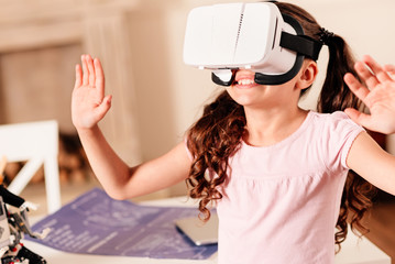 It cant be real. Amazed preteen child gesturing and smiling cheerfully while wearing a VR headset indoors.