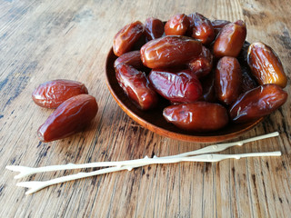 Dates in a wooden plate on a wooden table