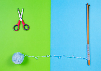 Blue yarn ball and knitting needles on colorful background