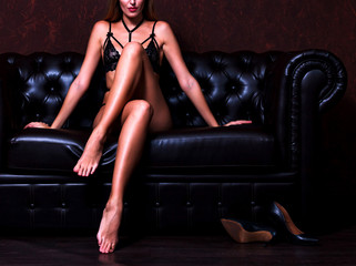 Sexy young woman with long legs sitting on a dark brown leather sofa