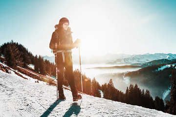 Fotomurales - Woman hiking along a snowy mountain road in winter