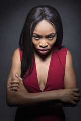 Black female model on a dark background with angry expressions.