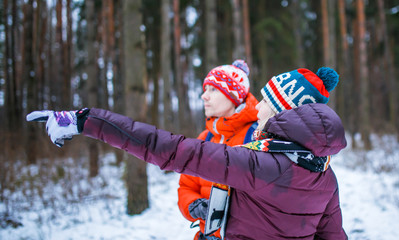 Image of man and woman showing hand forward in winter forest