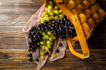 Picture of grapes green and black in wooden basket on table