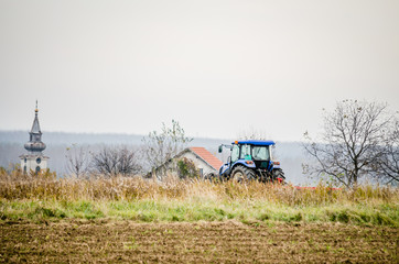 Modern tractor is working in the field