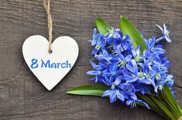 Blue Scilla flowers and decorative wooden heart on old wooden background for 8 March International Women's Day with copy space.First spring flowers.Springtime concept. Selective focus.