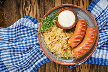 Plate of sausages and sauerkraut on wooden table. Traditional Oktoberfest menu. Flat lay. Top view.