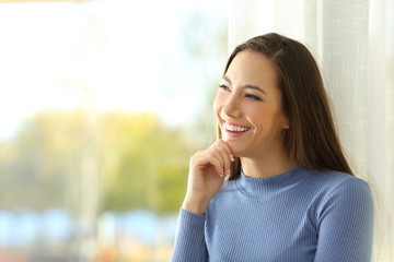 Smiley woman thinking and looking at side