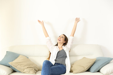 Happy woman raising arms and looking above on a couch