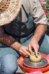 Creating clay jar by hands with potter wheel