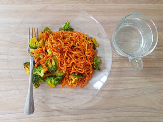 Top view, Spicy korean instant noodles with green vegetable, broccoli on plate with fork and glass of water on wood table with natural light background.